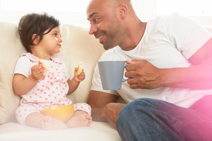 Baby girl and father sitting on sofa eating snackの写真素材 [FYI03576855]