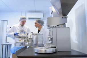 Operators using capsule filling machine in pharmaceutical factoryの写真素材 [FYI03576927]