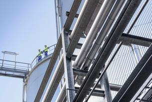 Worker on top of storage tanks in oil blending factoryの写真素材 [FYI03576989]