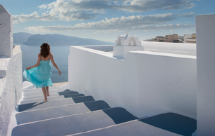 Woman walking down steps, Santorini, Cyclades, Greeceの写真素材 [FYI03577051]