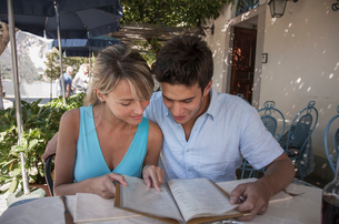 Couple looking at menu at outdoor restaurant, Lake Maggiore, Italyの写真素材 [FYI03577083]