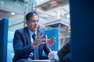 Two businessmen having meeting in office atriumの写真素材 [FYI03577256]