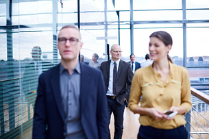 Businessmen and woman walking and talking on office balconyの写真素材 [FYI03577305]