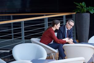 Businesswoman and man having meeting on office balconyの写真素材 [FYI03577335]