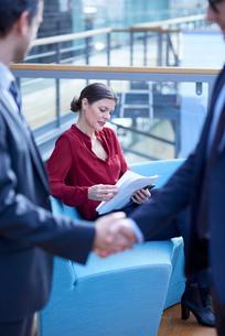 Businessmen shaking hands looking at businesswoman reading paperwork in office atriumの写真素材 [FYI03577352]