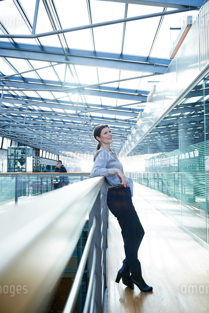 Happy businesswoman leaning against office balconyの写真素材 [FYI03577387]