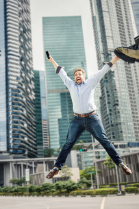 Happy businessman jumping for joy by city skyscrapersの写真素材 [FYI03577494]