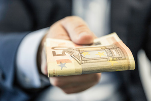 Close up of businessman's hand handing folded fifty euro notesの写真素材 [FYI03577510]