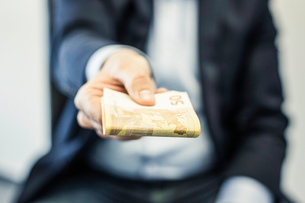 Businessman's hand handing folded fifty euro notesの写真素材 [FYI03577511]