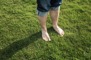 Legs and bare feet of man standing on green grassの写真素材 [FYI03577513]