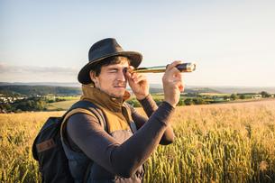 Mid adult man, standing in field, looking through telescope, Neulingen, Baden-W・ttemberg, Germanyの写真素材 [FYI03577521]