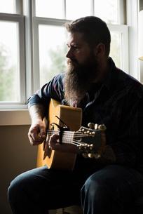 Man playing guitar beside windowの写真素材 [FYI03577534]
