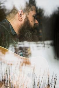 Man with guitar beside windowの写真素材 [FYI03577536]