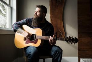Man playing guitar beside windowの写真素材 [FYI03577537]
