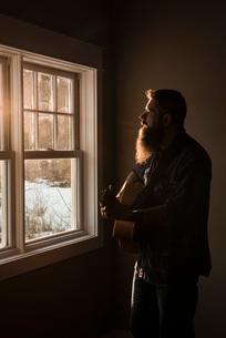 Man playing guitar beside windowの写真素材 [FYI03577539]