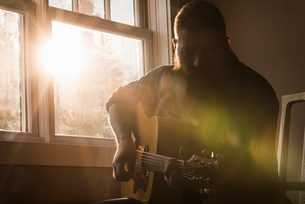 Man playing guitar beside windowの写真素材 [FYI03577540]