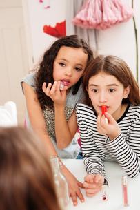Girls applying makeup in mirrorの写真素材 [FYI03577575]