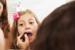 Girls applying makeup in mirrorの写真素材 [FYI03577608]