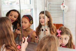 Girls applying makeup in mirrorの写真素材 [FYI03577610]