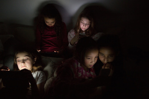 Girls in darkness at slumber party illuminated by digital tabletの写真素材 [FYI03577613]