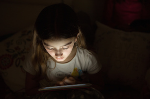 Girl in darkness illuminated by light from digital tabletの写真素材 [FYI03577615]