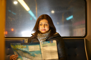 Woman travelling on bus looking at mapの写真素材 [FYI03577635]