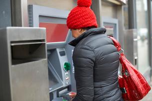 Woman using cash machineの写真素材 [FYI03577639]