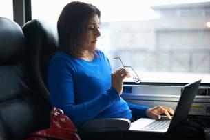 Woman travelling on train using laptopの写真素材 [FYI03577640]