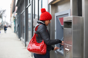 Woman using cash machineの写真素材 [FYI03577641]