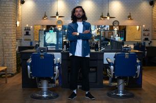 Portrait of barber with arms folded in retro style barber shopの写真素材 [FYI03577669]
