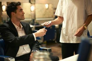 Businessman handing cash to barber in barber shopの写真素材 [FYI03577682]