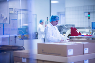 Workers packaging pharmaceutical products on production line in pharmaceutical plantの写真素材 [FYI03577722]