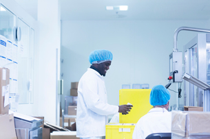 Workers packaging pharmaceutical products in pharmaceutical plantの写真素材 [FYI03577724]