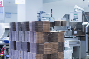 Flat-packed packaging stacked in pharmaceutical plantの写真素材 [FYI03577727]