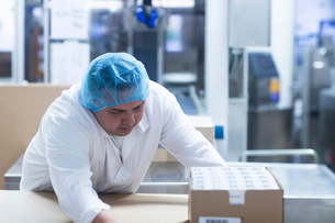 Worker packaging pharmaceutical products in pharmaceutical plantの写真素材 [FYI03577734]