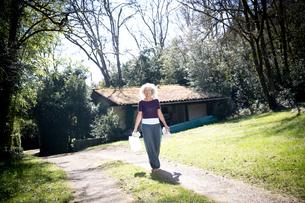 Mature female gardener carrying water and egg box in gardenの写真素材 [FYI03577911]