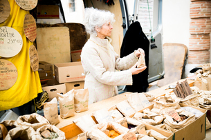 Mature female stall holder selling dried foods at local french marketの写真素材 [FYI03577942]
