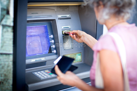 Mature woman inserting credit card into local french cash machineの写真素材 [FYI03577949]