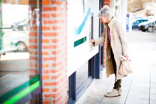 Mature woman using local french cash machineの写真素材 [FYI03577950]