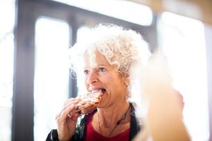 Woman eating pastryの写真素材 [FYI03578014]
