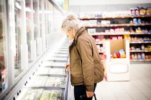 Mature woman in supermarket, looking in freezer cabinetの写真素材 [FYI03578020]