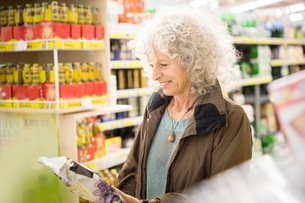 Mature woman in supermarket, reading back of packagingの写真素材 [FYI03578033]