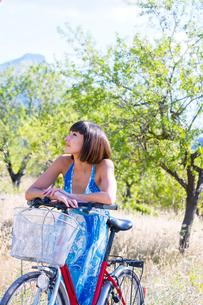 Woman leaning on push bike in countryside, Mallorca, Spainの写真素材 [FYI03578093]