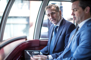 Two businessmen looking at smartphone on double decker busの写真素材 [FYI03578150]