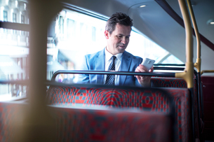 Businessman looking at smartphone on double decker busの写真素材 [FYI03578152]