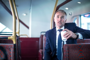 Businessman with takeaway coffee on double decker busの写真素材 [FYI03578153]