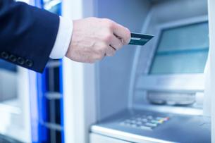 Man using cash machineの写真素材 [FYI03578172]