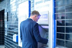 Man using cash machineの写真素材 [FYI03578173]