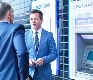 Businessmen talking by cash machineの写真素材 [FYI03578175]