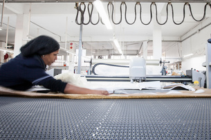 Female factory worker preparing textile for machinery in clothing factoryの写真素材 [FYI03578209]